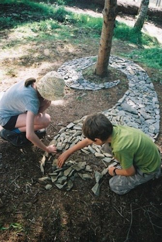 children place stones around a tree