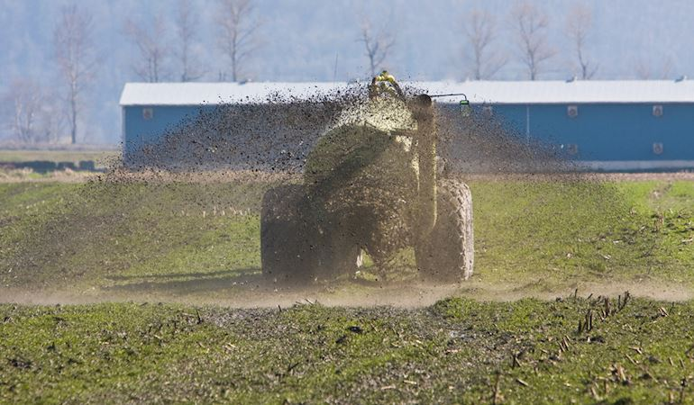 Tractor muck spreading on a farm