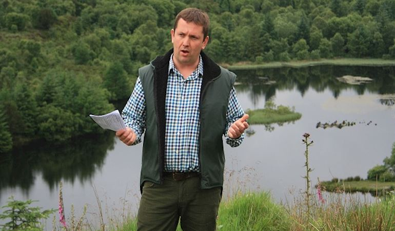 Man in checked shirt and waistcoat stood at the side of a lake with piece of paper in his hand