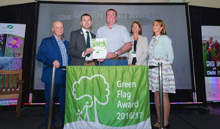 a group of 5 people standing behind a green flag awards 2016-17 banner