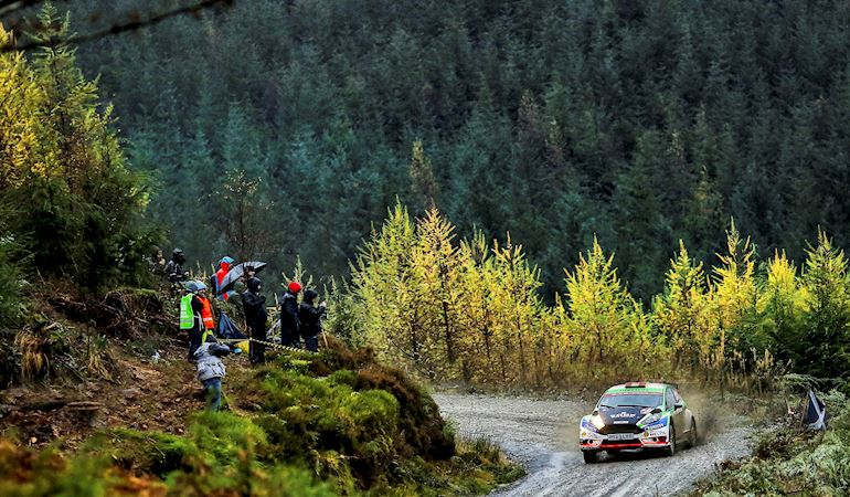 Rally car on mountain road with trees in the background