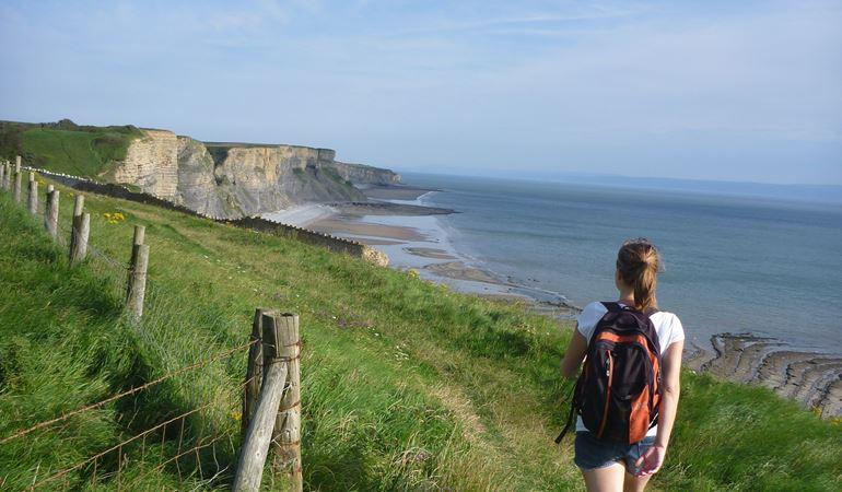 Woman walking along a coastal path