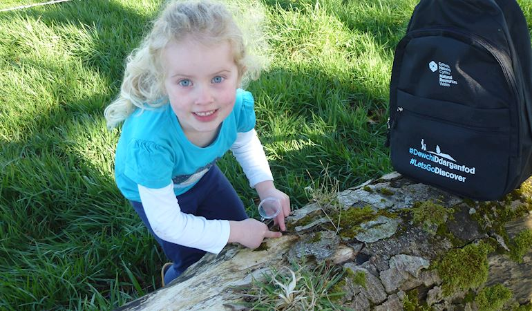 Little girl using a bug pot to collect insects next to a discovery backpack