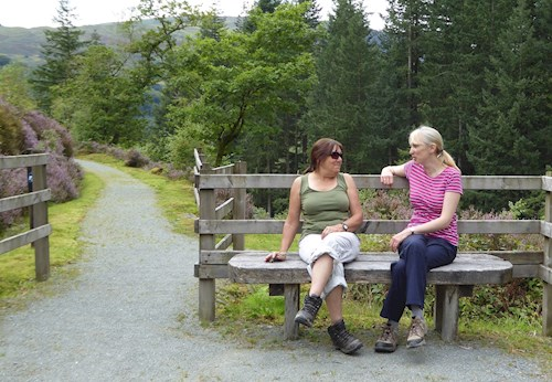 Two women on bench on Glasdir Trail