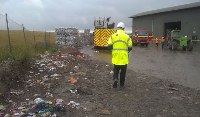 NRW officer at the landfill site with fire engine and waste in the background