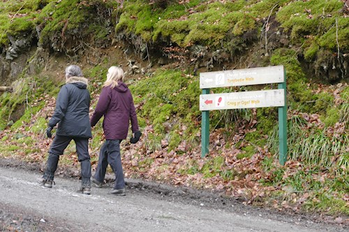 Two women walking past a sign