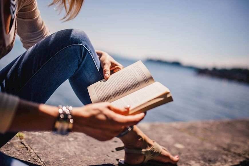 Woman reading a book next to water
