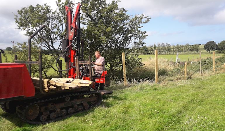 Photo of a man driving a large fence post machine next to Afon Wygyr with newly installed posts behind him