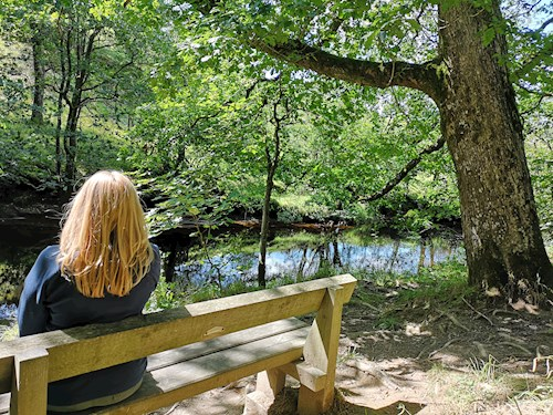 Woman on bench by river