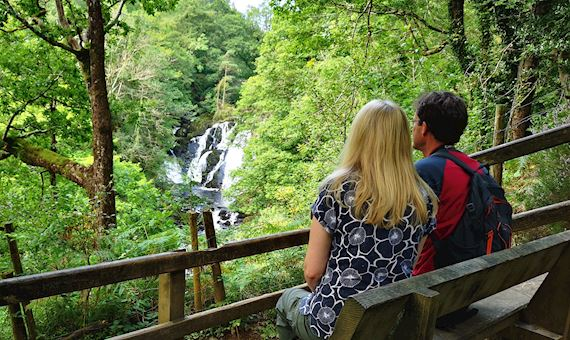 Man and woman looking at Swallow Falls waterfall