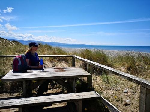 Woman at viewpoint looking at beach