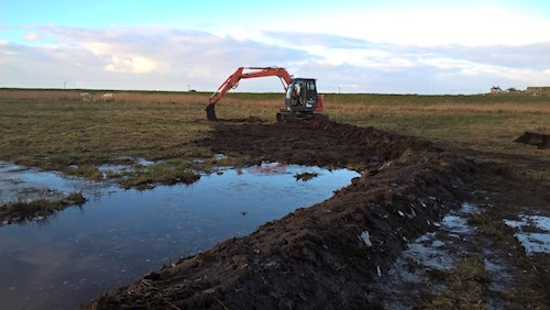 Machine digging low level banks of peat