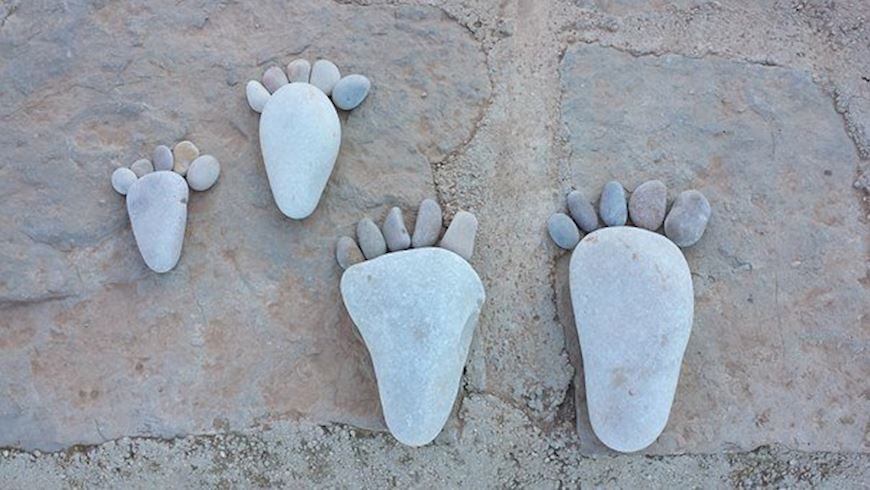 Feet made of stones design on a beach