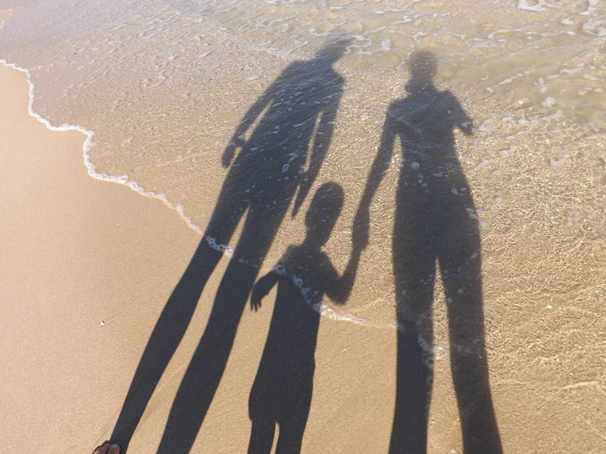 Shadows on a beach 2 adults and a child