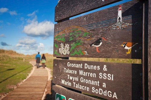 View of boardwalk at Gronant Dunes with Site of Special Scientific Interest sign prominant in foreground