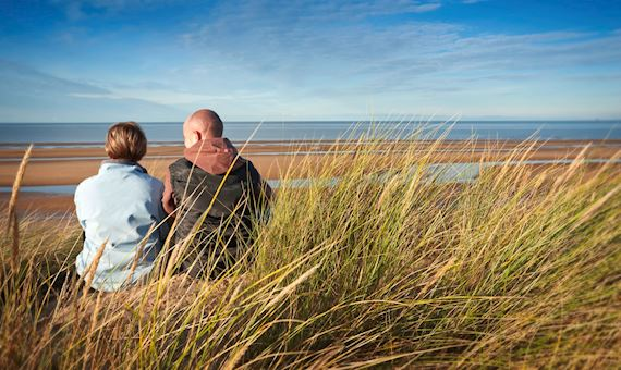 Couple Sitting On Grass At Gronant Dunes
