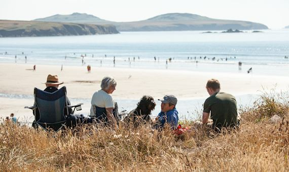 A Family Sat In The Dunes At Whitesands Pembrokeshire, With A Busy Beach Behind Them.