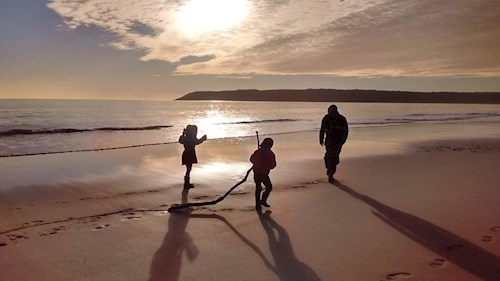 A family playing on the beach at sunset in Tor Bay, Gower
