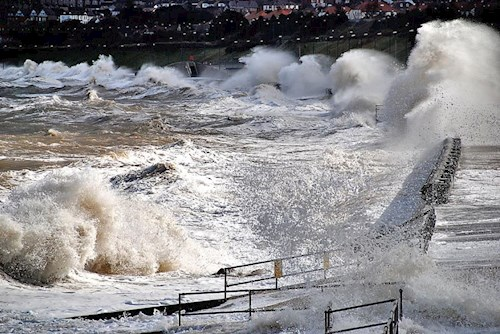 Coastal storm surge at Colwyn Bay with coastal defences visible.