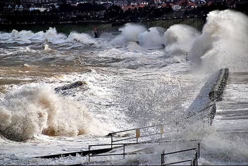 Ymchwydd storm arfordirol ym Mae Colwyn gydag amddiffynfeydd arfordirol i'w gweld.
