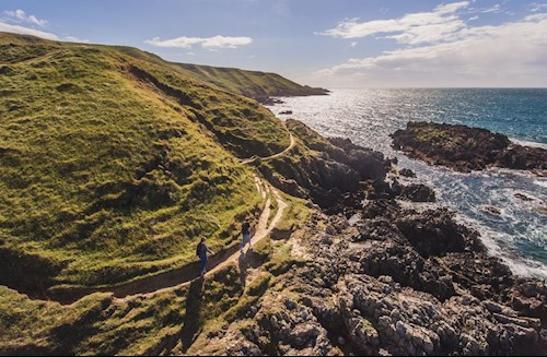 A Pair Of Walkers On The Wales Coastal Path At Porthor, Llŷn Peninsula Where Rugged Green Hills Meet The Sea