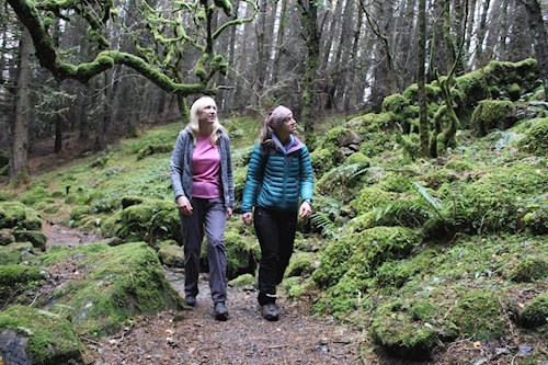 Two women walking through forest on the Geirionydd to Crafnant Trail