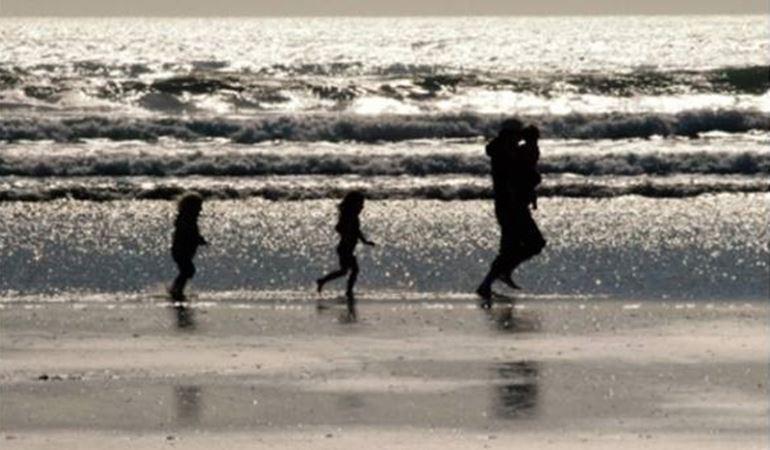 Photo of a family running on a beach near the sea