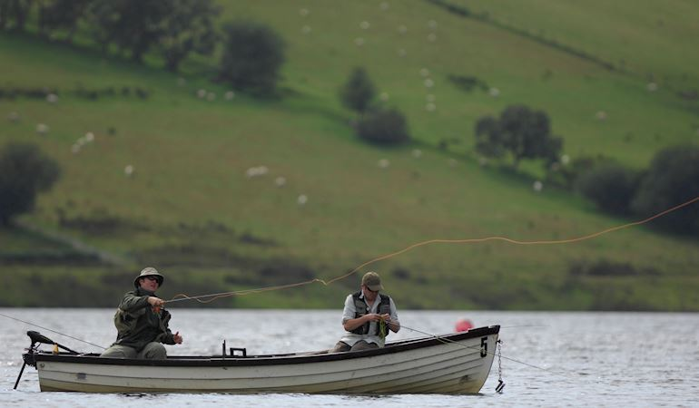 Two men sat in a boat on a river fishing