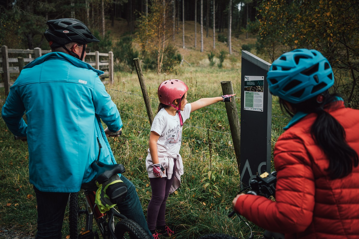 Child pointing at sign with parents on bikes