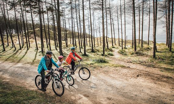 Family cycling in Newborough Forest