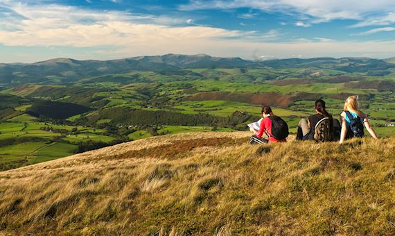 Three walkers resting on summit of Foel Fadian looking north to Cadair Idris Cambrian Mountains