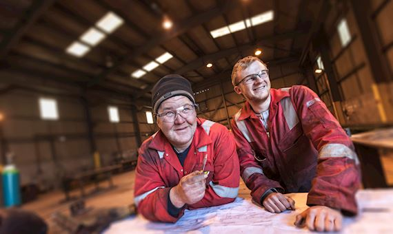 Two employees looking at a document plan at Jenkins and Davies Engineering, Haven Waterway enterprise zone, Pembrokeshire West energy and environment sector