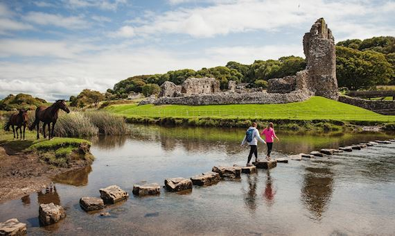 mother and daughter on stepping stones in a river walking towards a castle