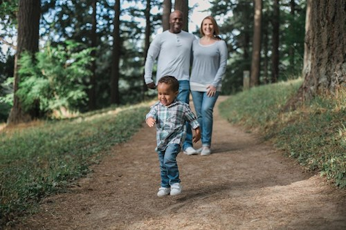 A man, woman and small boy go for a walk in a woodland