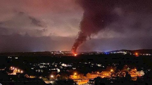Image of fire and black smoke rising from a long distance away.