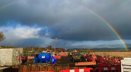 Site during rail recovery. A rainbow is in the sky.