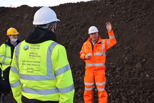 Image of three workers. The focus is on the person in the foregrounds jacket which has 'Keep your distance' on the back
