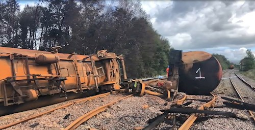 Derailed train laying on its side.