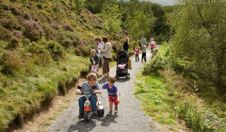 Families walking on a path at Bwlch Nant yr Arian